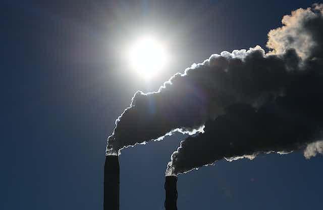Two plumes of smoke leaving industrial chimneys
