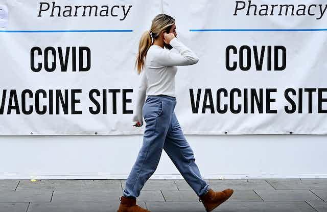 A woman walking past a COVID vaccine centre