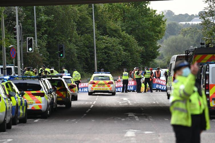 Police crowd demonstrators sat at an M25 junction.