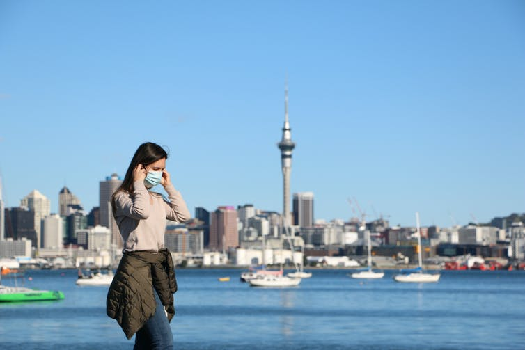 A woman in a mask on the waterfront in Auckland