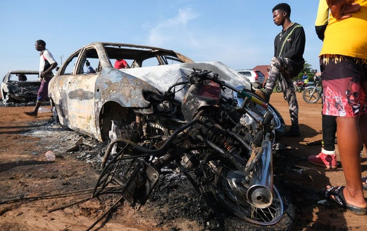 2 man standing beside the burnt remains of a car and some motorcycles.