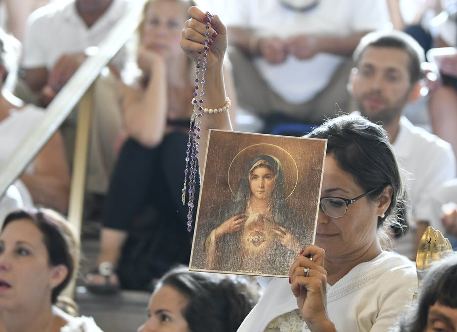 A woman holds a rosary and a picture of the Virgin Mary during a hearing challenging the constitutionality of New York State's repeal of the religious exemption to vaccination, in Albany, N.Y., Aug. 14, 2019.