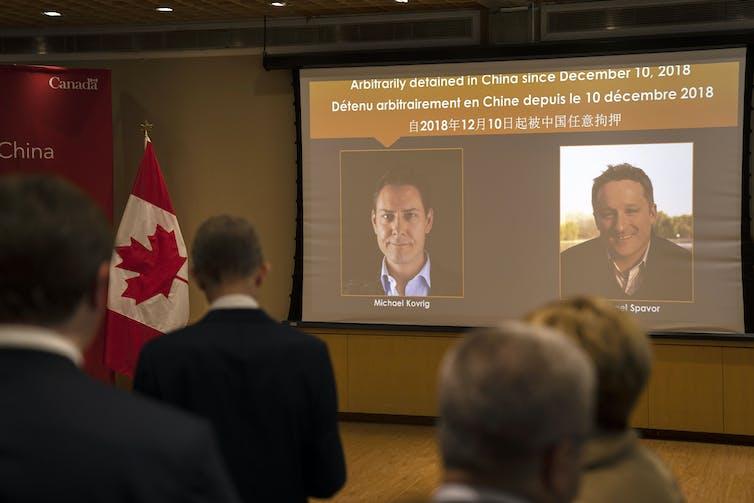 Un écran géant montre les photos de Michael Kovrig et de Michael Spavor