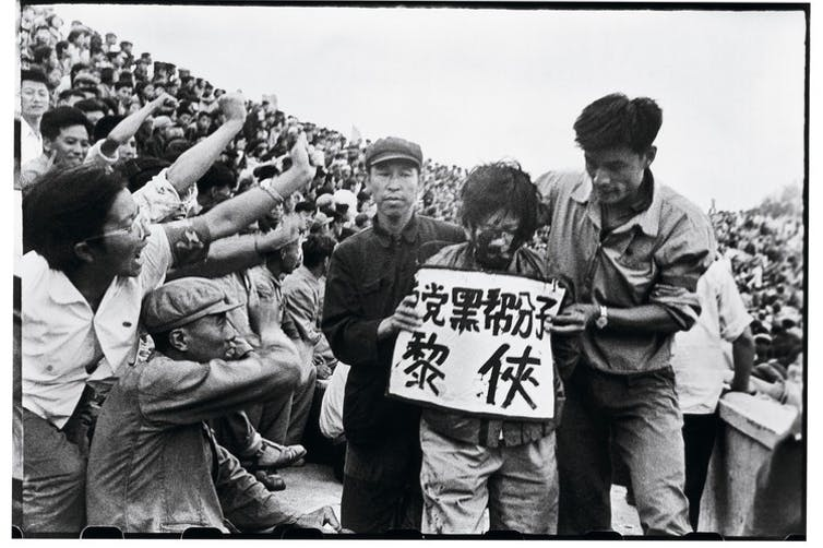 Black and white photo of Chinese man with a placard around his neck led through a jeering crowd throwing ink in his face.