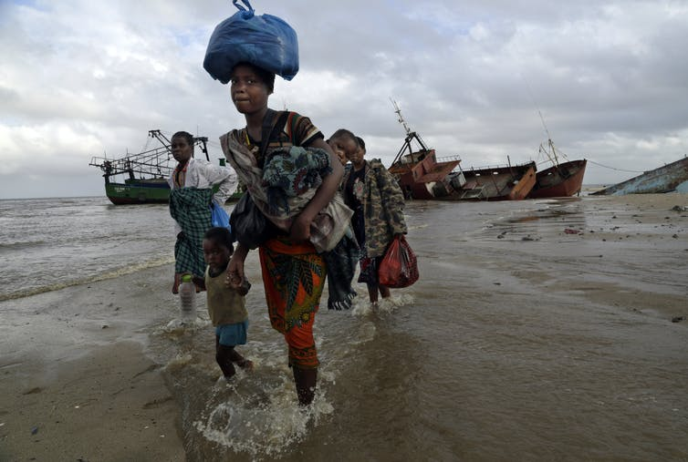 People Walk Along A Beach With Bags On Their Heads And Belongins In Their Arms After Being Rescued From A Flooded Area