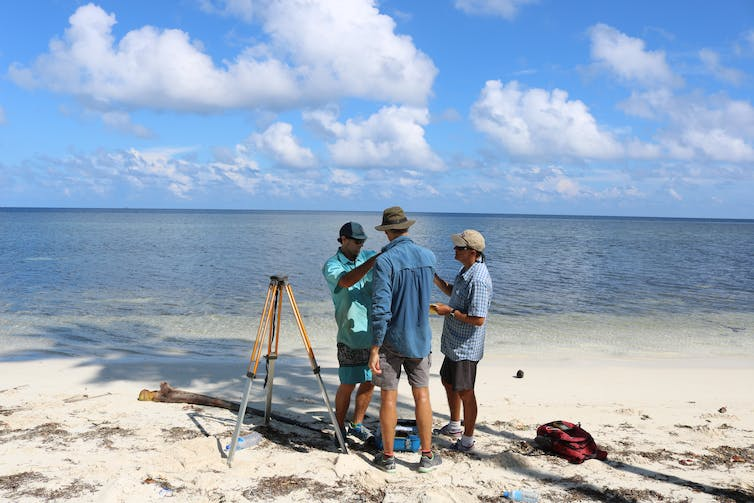 three people working on a shoreline