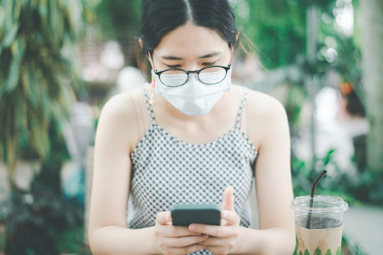 Young woman wearing mask scrolling smartphone sitting outside