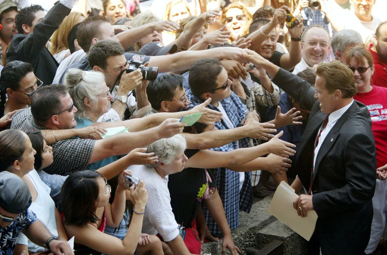 Arnold Schwarzenegger greets supporters with outstretched arms during the 2003 California recall election.