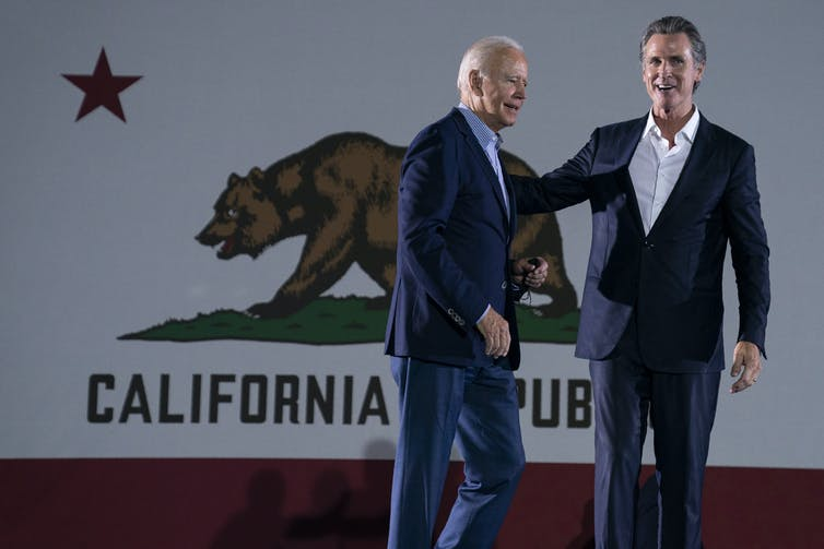 President Joe Biden greets California Gov. Gavin Newsom in front of a large California flag.