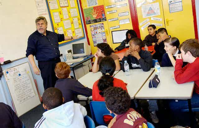 A teacher teaches a creative writing lesson in a primary school classroom