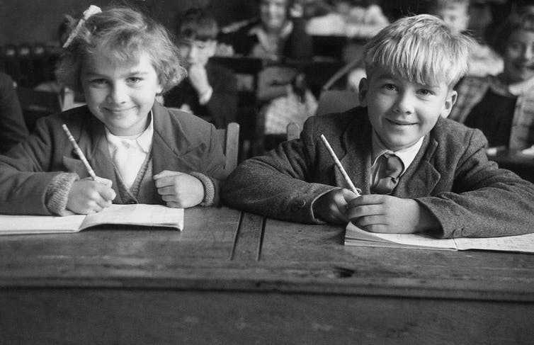 A boy and girl in 1950s school uniforms sit at their desks holding pencils and smiling