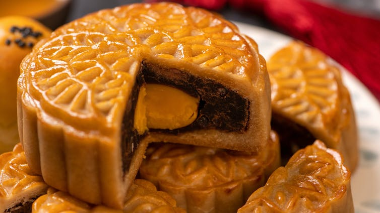 Plate of mooncake slices with yolk center.