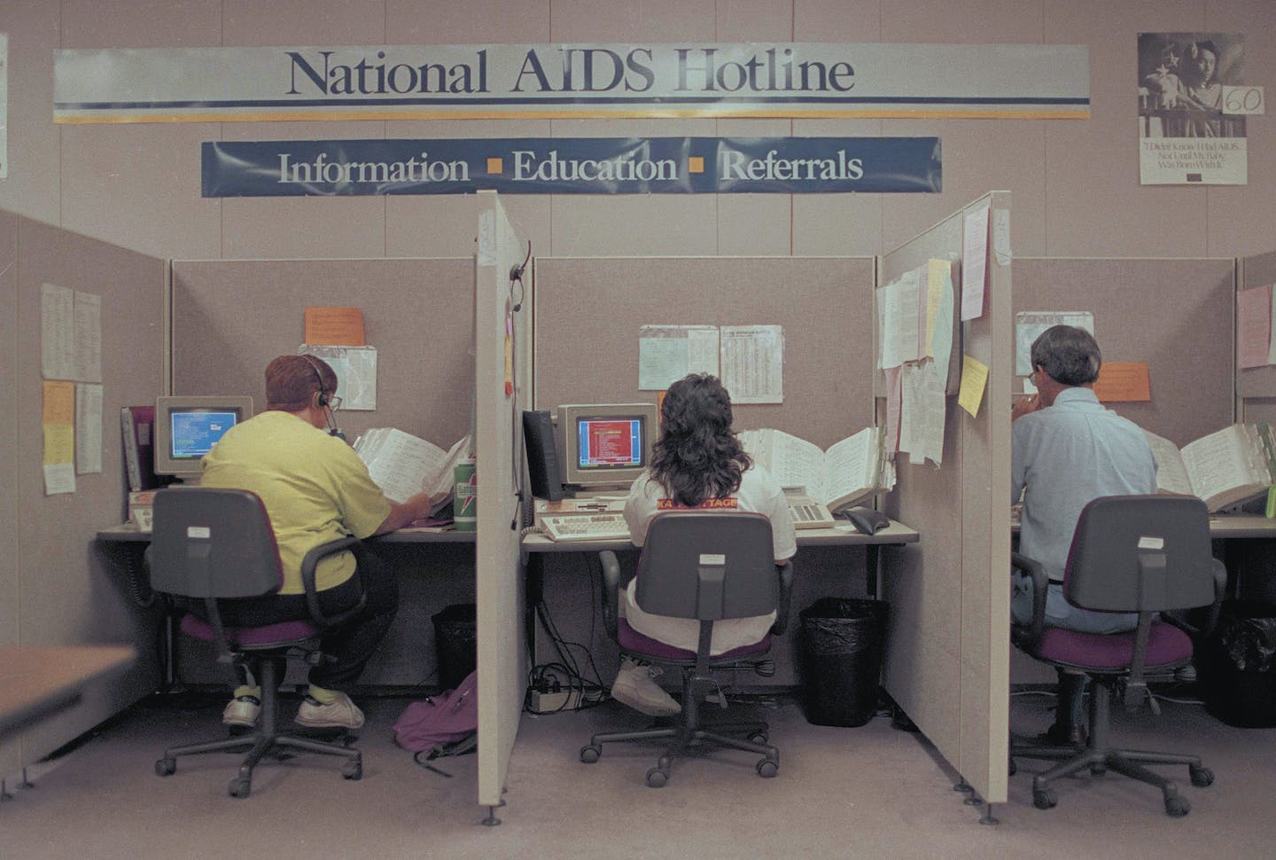 Three people at cubicle desks under a banner reading 'National AIDS Hotline - Information, Education, Referrals.'