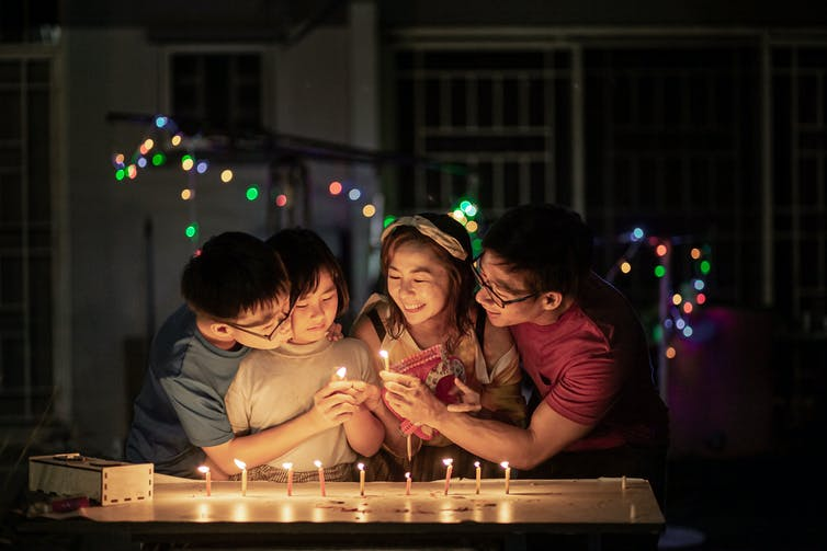 Group of smiling people gathered around lit candles at night.