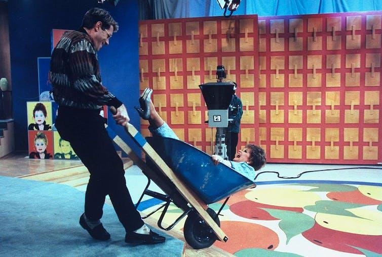 Man pushing a wheelbarrow with a woman in it.