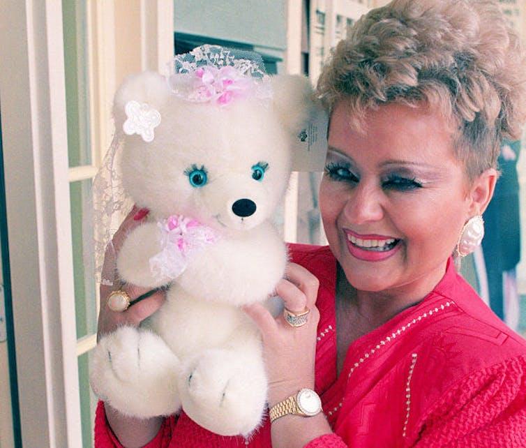 Woman smiles holding a stuffed bear.