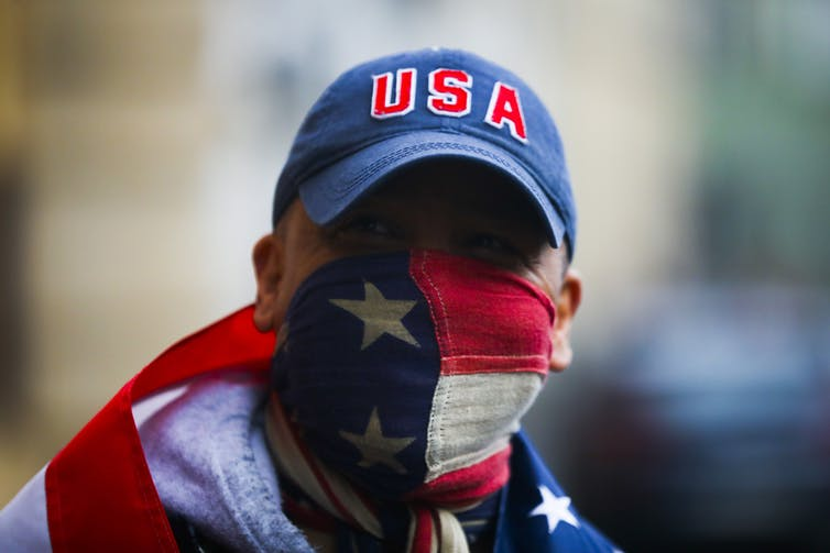 man in USA cap with American flag mask and another flag around shoulders