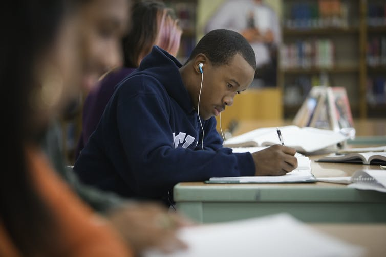 A Black male teenager studies at a library while listening to music through his earphones.