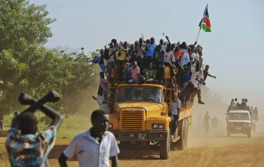 Residents hang from a bus and hold a South Sudanese flag in the disputed Abyei region of Sudan.