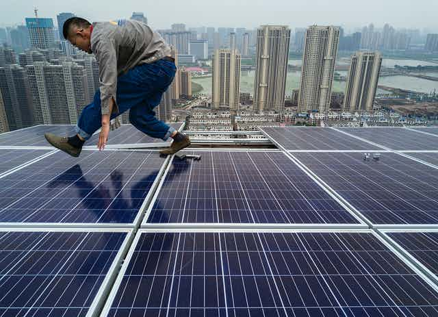 A man hunches over as he walks across solar panels on a skyscraper rooftop with a city of tall buildings along a port in the background.