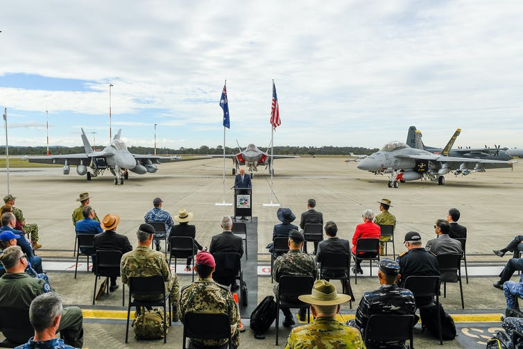 Fighter jets and US and Australian flags in background of official ceremony on airstrip.