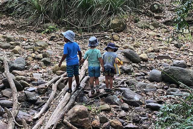 Three children playing in a dry stony creek bed