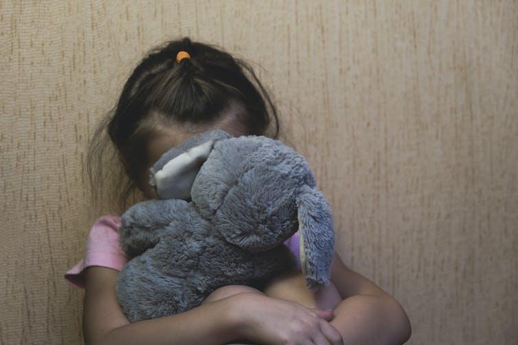 Child hides behind stuffed toy