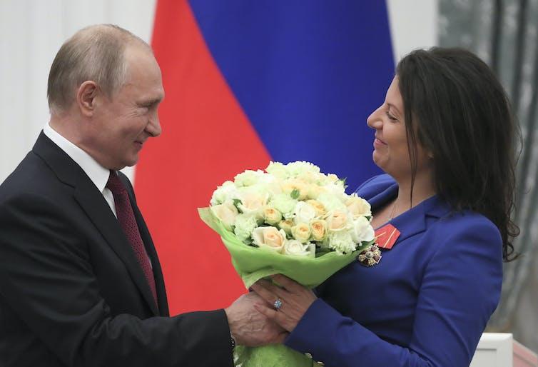 Russian president, Vladimir Putin, presents RT editor-in-chief Margarita Simonyan with a bunch of flowers.