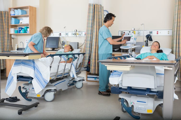 Two nurses are tending to two patients laying in hospital beds.