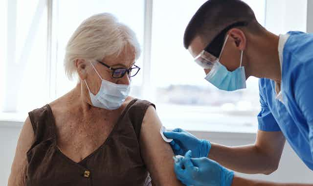 A nurse vaccinating a woman for COVID-19