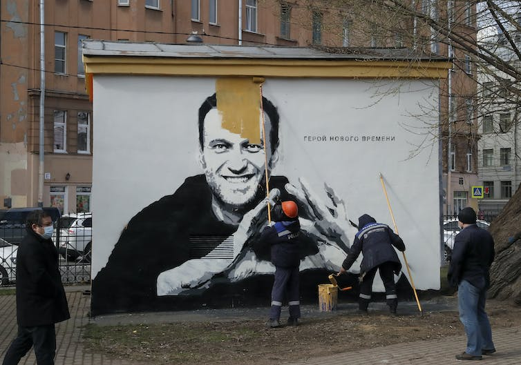 Russian municipal workers paint over a picture of jailed opposition leader Alexei Navalny.