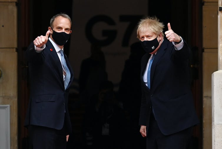 Dominic Raab et Boris Johnson, tous deux portant des masques faciaux, se retournent et lèvent le pouce à la caméra alors qu'ils entrent dans la conférence du G7.