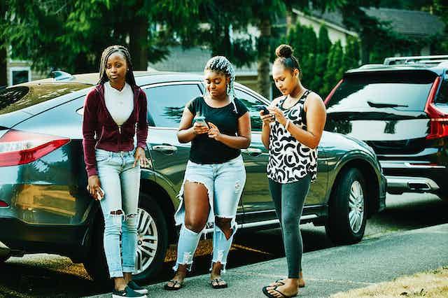 Three teenage girls on a sidewalk looking at smartphones