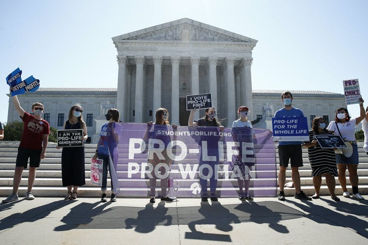 A group of people holding signs in front of the Supreme Court building
