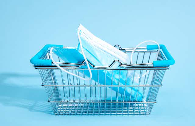 A small shopping cart with a mask in it with a blue background