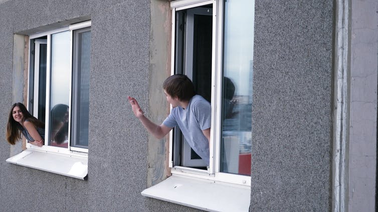 Neighbours in adjacent apartment wave to each other.