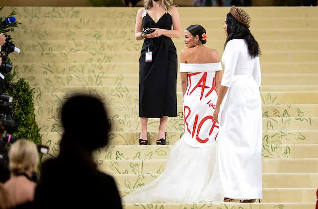"""Congresswoman Alexandria Ocasio-Cortez  walks up the stairs at the Met Gala wearing a white dress with """"Tax the Rich"""" written on it."""