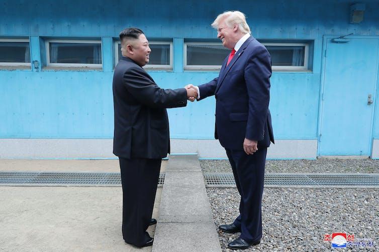 Donald Trump et Kim Jong-un se serrent la main et sourient.