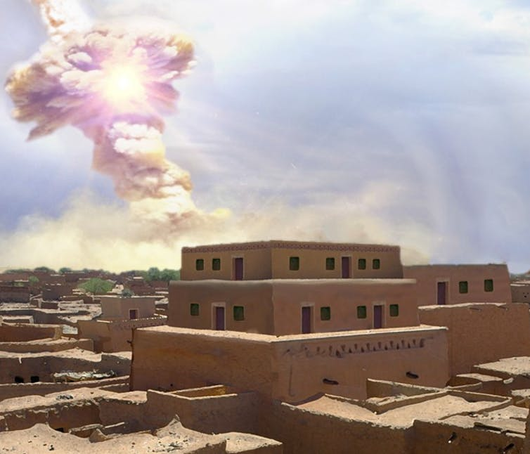 Brilliant explosion in midair above square-topped adobe buildings.