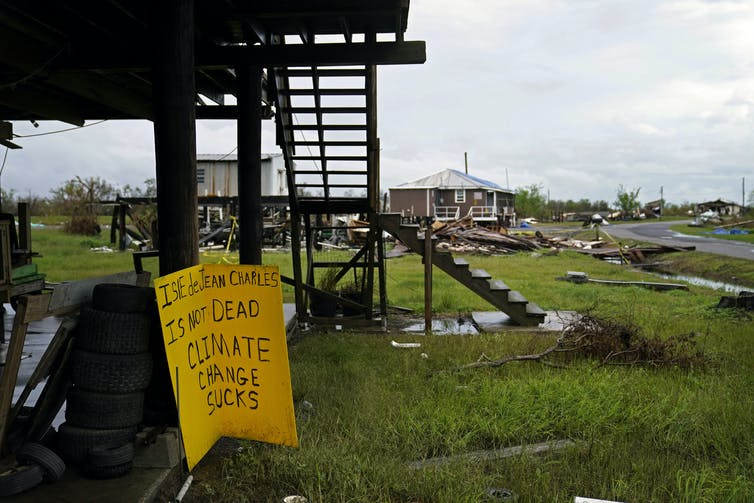 severely damaged houses and a sign that read: 'Ile de Jean Charles is not dead.  Climate change sucks.
