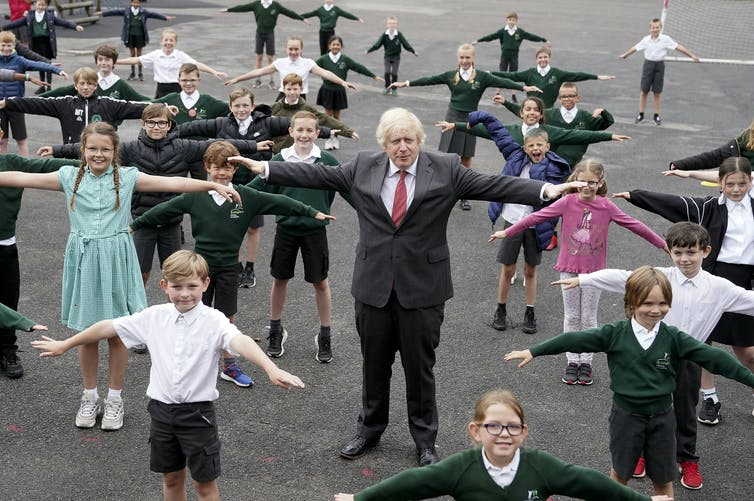 Man in suit stands among children with outstretched arms as they demonstrate physical distancing
