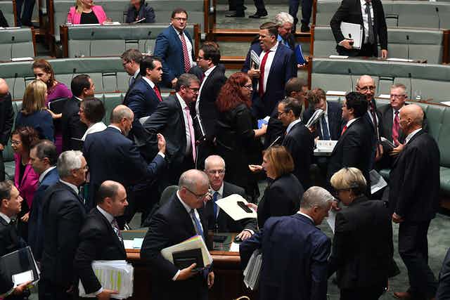 Federal MPs cross during a parliamentary division.