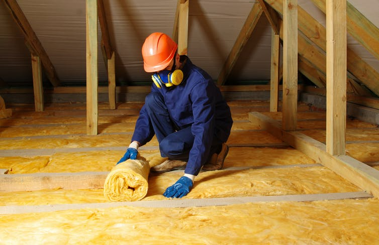A worker in blue overalls rolls out wool in an attic.