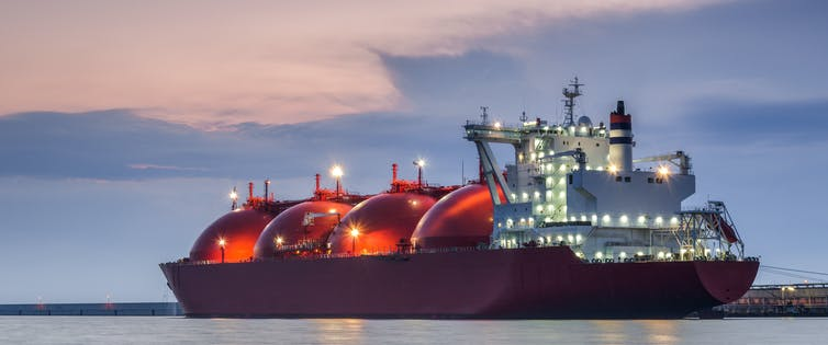 A large tanker vessel with red, bulbous tanks for LNG.