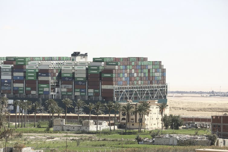 The Ever Given cargo ship loaded with shipping containers appear stuck in the mud along the Suez Canal in March 2021