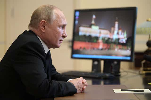 Russian President Vladimir Putin sits at a desk as news of the Russian parliamentary elections plays on a TV.
