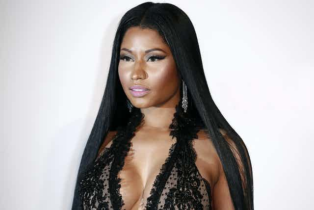 Nicki Minaj has long black hair and a light pink lipstick on with smokey eyeshadow. She's staring off into the distance in what looks like a red carpet photo
