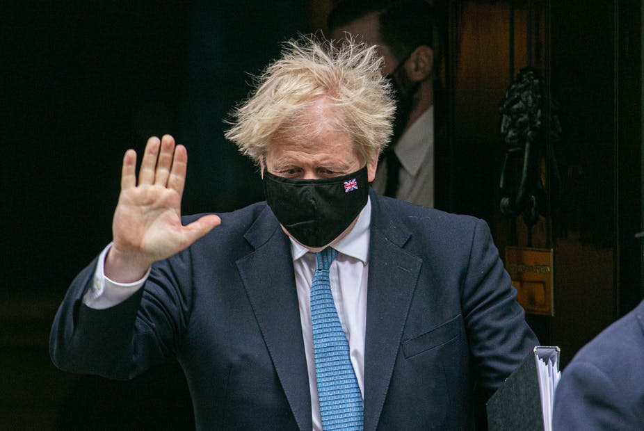 Boris Johnson in facemask holds up hand
