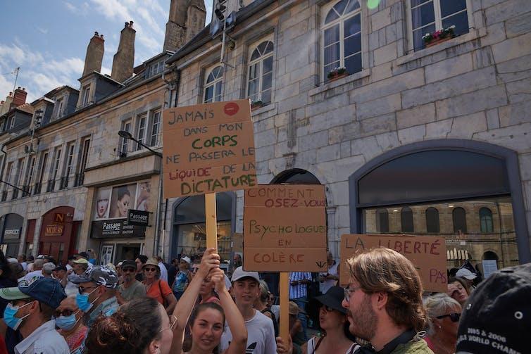 Manifestantes brandissant des pancartes contre la vaccin lors d'une manifestation à Besançon le 14août 2021