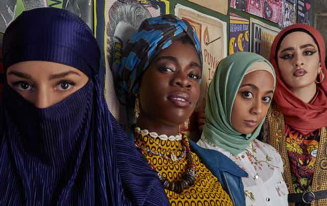 Five girls of diverse ethnicity, most wearing head coverings, stand by a wall.